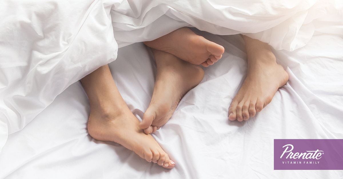 Two sets of feet in bed