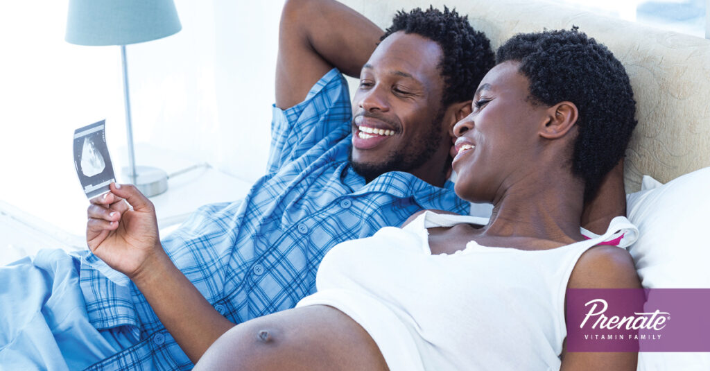 Couple in bed looking at an ultrasound