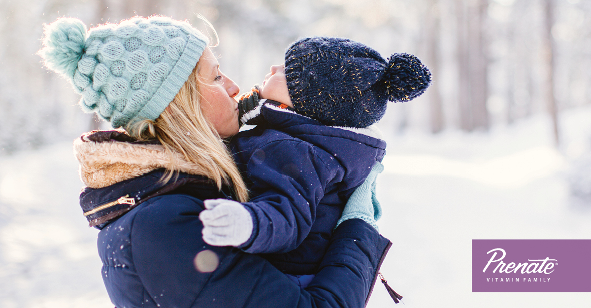 Mother holding child outside in winter
